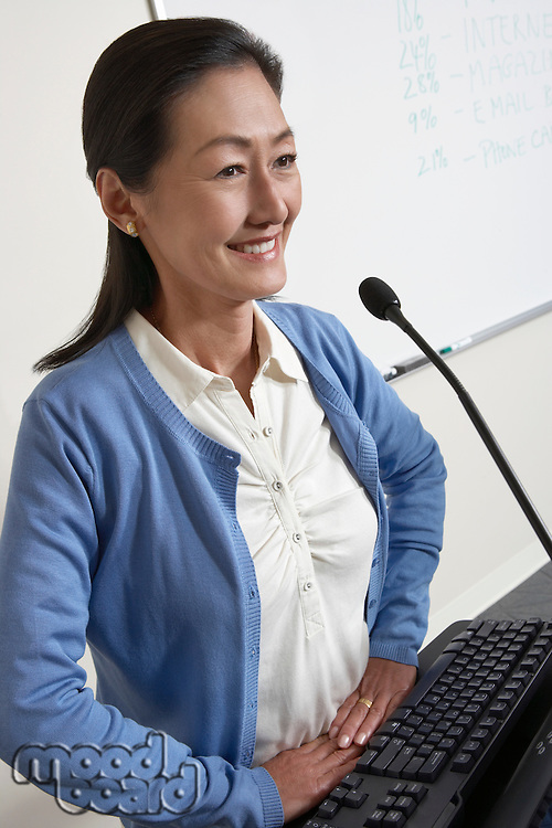 Female teacher smiling in lecture theatre