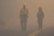 U.S. Park Ranger, DWAYNE GRUVER (left) and Hotshot KRISTEN ALLISON (right), walk along Hetch Hetchy Road as smoke from the Rim Fire nearly obscures the road behind them on Sunday, September 8, 2013. Flames rose from the Tuolumne River canyon below O'Shaughnessy Dam and crossed Hetch Hetchy Road behind  GRUVER and ALLISON.