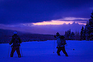 Two men cross country skiing at dusk at Togwotee Pass, Bridger Teton National Forest in a overcast day  in winter.  Grand Teton Range is in the background. Model Released #0012010, #0022010