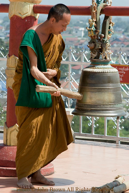 A Buddhist monk is ringing a bell with a piece of wood at the beautiful Shwe Dagon Pagoda temple in Tachilek, Burma (Myanmar).