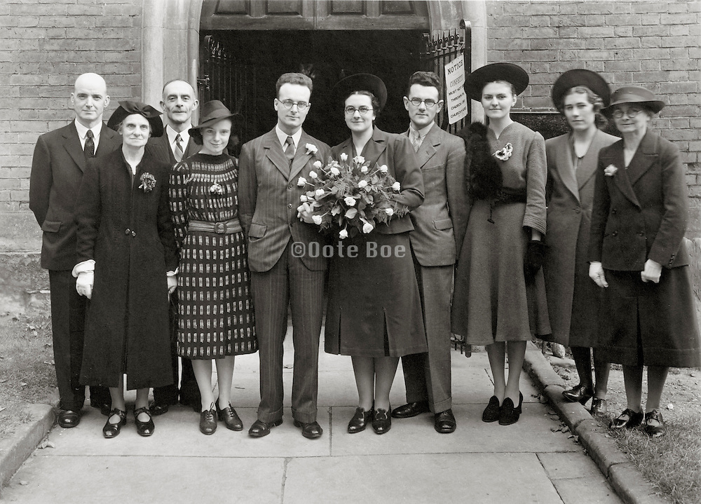 group family wedding photo in front of the church door opening England 1940s