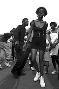 A slim woman walks towards the camera at Notting Hill Carnival, 1991.