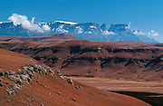 Mamndeni Valley with the winter colours of rooigras (Themeda triandra) and black fire break from a controlled burn. Beyond (L to R) Old Woman Grinding Corn 2986m, Ship's Prow Pass, snow-covered Champagne Peak 3377m, Monk's Cowl 3234m, Cathkin Peak 3149m. From Chimney Pot (Maqomfa) 1894m. Ukhahlamba-Drakensberg Park, KwaZulu-Natal, South Africa.  Nikon F4, 28-70/3.5-4.5D. Kodak E100S. July 1997.