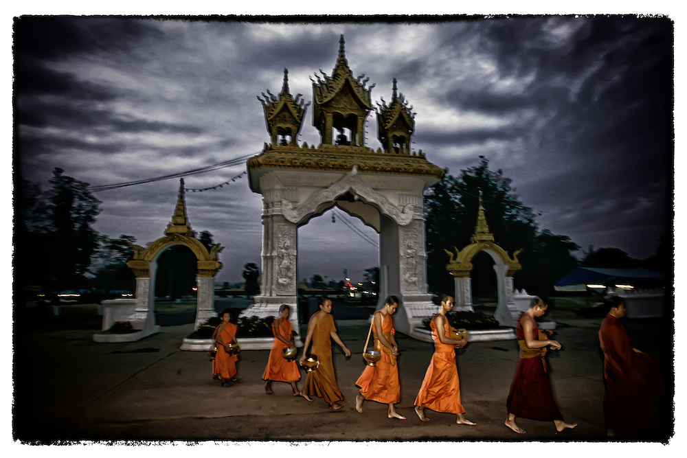 Laotian Buddhist monks walk on their early morning rounds in Vientiane, Laos.