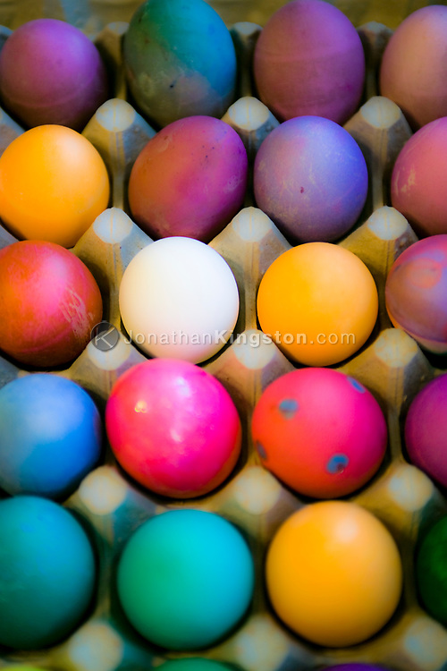Colorful Easter eggs in a cardboard egg crate.