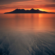 Laig bay on Eigg has arguably one of the most memorable views in Scotland. From this vantage point Rums' Cuillin form a sublime symmetry and watching the sun dip behind with the patterns of light sand being dragged back over the black layer beneath, complete a picture for me of Scotland at its most sublime.