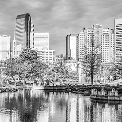 Charlotte skyline black and white panorama photo with Marshall Park pond, Duke Energy Center and One Wells Fargo Center buildings. Charlotte, North Carolina is a major city in the Eastern United States of America.