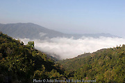 White clouds provide a blanket of fog below them for the rural town of Pai, Thailand.