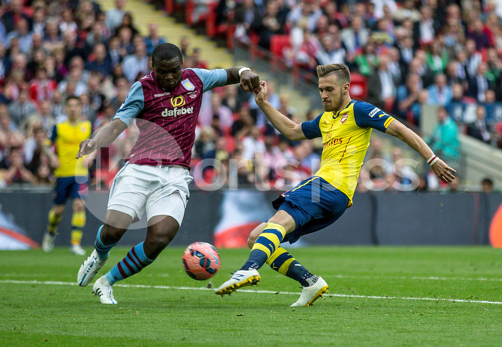 Aaron Ramsey of Arsenal lets rip before the challenge of Jores Okore of Aston Villa during the The FA Cup Final match between Arsenal and Aston Villa at Wembley Stadium, London, England on 30 May 2015. Photo by Liam McAvoy.