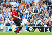 Brighton and Hove Albion midfielder Anthony Knockaert (11) beats Manchester United Defender Luke Shaw to the ball and crosses during the Premier League match between Brighton and Hove Albion and Manchester United at the American Express Community Stadium, Brighton and Hove, England on 19 August 2018.