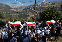 © Licensed to London News Pictures. 17/08/2020. Beirut, Lebanon. A funeral procession for three firefighters Charbel Hitti, cousin Najib Hitti and uncle Charbel Karam, who died in the huge explosion in Beirut Port on 4 August, makes its way through Bir El Hait, a mountainous region of Lebanon, before arriving at the family's home town of Qartaba for a funeral and ceremony. The three family members were said to be best friends. Photo credit : Tom Nicholson/LNP