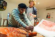 Woluwe-Saint-Lambert. 20 februari 2013 Jongeren bezig met houtsnedes in jongerencentrum Antichambre asbl - Zij zullen na het drukken van de houtsnedes op grote vellen papier, in het mim, muziekinstrumentenmuseum , een performance ondersteunen tijdens de museum nightfever.Het inkten van de houtsnede.