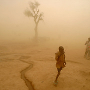 June 8, 2004 - Zalingei, West Darfur - IDP's (Internally Displaced People) try to take shelter during a sandstorm at the Zalingei IDP camp. CARE, an international aid organization, is feeding 48,000 displaced people in Zalingei and 400,000 IDP's throughout Darfur. Photo by Evelyn Hockstein/CARE.