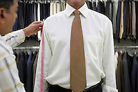 Tailor measuring business man with tape measure mid section