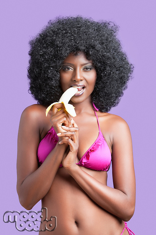 Flirtatious young woman in bikini eating banana against violet background