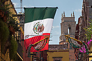 Mexican flag flutter against a blue sky and classic colonial building along Calle Zacateros in the historic district of San Miguel de Allende, Mexico.