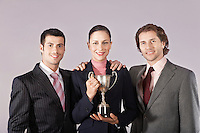 Businesswoman holding trophy with male colleagues portrait