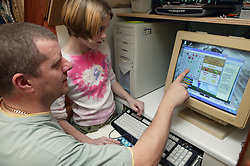 Single parent showing young daughter a game on the computer screen at home,