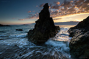 Sunset through a rocky channel on Anglesey's North West coast. Holyhead Mountain in the background.