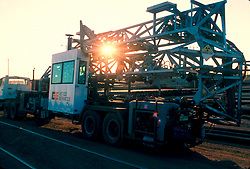 Large transport truck delivering metal structures at sunset