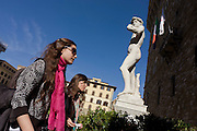 "Two female tourists walk beneath the perfect nude male example of Michelangelo's David statue in Piazza della Signoria. It is said that the statue's genitals were created smaller to imply that David was not allowing himself to make decisions with pleasure in mind. ""David"" is a masterpiece of Renaissance sculpture created between 1501 and 1504, by the Italian artist Michelangelo. It is a 5.17 metre (17 feet) marble statue of a standing male nude. The statue represents the Biblical hero David, a favoured subject in the art of Florence but soon came to symbolise the defence of civil liberties in the Florentine Republic, an independent city-state threatened on all sides by more powerful rival states and by the Medici family."