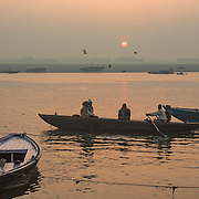 Hindu devotees take boats down the Ganges River at sunrise at Varanasi, Uttar Pradesh, India.