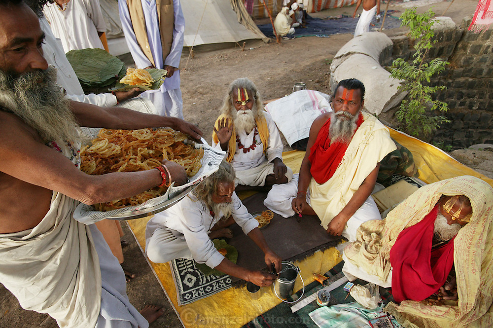 Distributing food to Ashram members during KUMBH MELA in Ujjain, Madhya Pradesh, India. The Kumbh Mela festival is a sacred Hindu pilgrimage held 4 times every 12 years, cycling between the cities of Allahabad, Nasik, Ujjain and Hardiwar. Kumbh Mela is one of the largest religious festivals on earth, attracting millions from all over India and the world. Past Melas have attracted up to 70 million visitors.