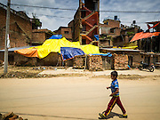 04 AUGUST 2015 - BUNGAMATI, NEPAL: A boy walks past buildings covered in tarps that were damaged in the earthquake in Bungamati, a village about an hour from Kathmandu. Three months after the earthquake many families still live in tents and temporary shelters scattered around the village. The Nepal Earthquake on April 25, 2015, (also known as the Gorkha earthquake) killed more than 9,000 people and injured more than 23,000. It had a magnitude of 7.8. The epicenter was east of the district of Lamjung, and its hypocenter was at a depth of approximately 15 km (9.3 mi). It was the worst natural disaster to strike Nepal since the 1934 Nepal–Bihar earthquake. The earthquake triggered an avalanche on Mount Everest, killing at least 19. The earthquake also set off an avalanche in the Langtang valley, where 250 people were reported missing. Hundreds of thousands of people were made homeless with entire villages flattened across many districts of the country. Centuries-old buildings were destroyed at UNESCO World Heritage sites in the Kathmandu Valley, including some at the Kathmandu Durbar Square, the Patan Durbar Squar, the Bhaktapur Durbar Square, the Changu Narayan Temple and the Swayambhunath Stupa. Geophysicists and other experts had warned for decades that Nepal was vulnerable to a deadly earthquake, particularly because of its geology, urbanization, and architecture.    PHOTO BY JACK KURTZ