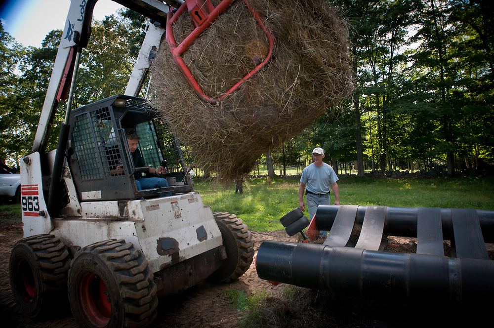 Presidential hopeful, former New Mexico Governor Gary Johnson tries his hand with the bobcat as he wraps round bales of hay  at the Miles Smith farm in Loudon, NH. 23rd of august 2011.