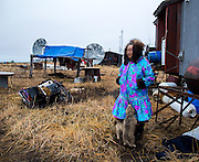 Lucy Adams stands outside of her home with two of her pups in Kivalina, Alaska. Kivalina is one of several villages undergoing coastal erosion due to climate change that will need to move in the next several years.