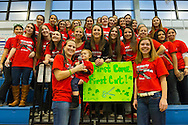 In front of sign, LORI BISCARDI, the coach of the girls soccer team at Calhoun High School, holds her daughter LIA BISCARDI, 2, as the soccer team poses for a photoholds her daughter LIA, 2, TheCalhoun High School girls soccer team, including these two members, are volunteers at the school's St. Baldrick's head shaving event. Calhoun exceeded its goal of raising $50,000 for childhood cancer research. Plus, many ponytails cut off will be donated to Locks of Love foundation, which collects hair donations to make wigs for children who lost their hair due to medical reasons.