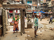06 AUGUST 2015 - KATHMANDU, NEPAL: A woman walks into the gate of Seto Machindranath Temple in Kathmandu even through the wall around the temple collapsed in the Nepal Earthquake. The Nepal Earthquake on April 25, 2015, (also known as the Gorkha earthquake) killed more than 9,000 people and injured more than 23,000. It had a magnitude of 7.8. The epicenter was east of the district of Lamjung, and its hypocenter was at a depth of approximately 15km (9.3mi). It was the worst natural disaster to strike Nepal since the 1934 Nepal–Bihar earthquake. The earthquake triggered an avalanche on Mount Everest, killing at least 19. The earthquake also set off an avalanche in the Langtang valley, where 250 people were reported missing. Hundreds of thousands of people were made homeless with entire villages flattened across many districts of the country. Centuries-old buildings were destroyed at UNESCO World Heritage sites in the Kathmandu Valley, including some at the Kathmandu Durbar Square, the Patan Durbar Squar, the Bhaktapur Durbar Square, the Changu Narayan Temple and the Swayambhunath Stupa. Geophysicists and other experts had warned for decades that Nepal was vulnerable to a deadly earthquake, particularly because of its geology, urbanization, and architecture.       PHOTO BY JACK KURTZ