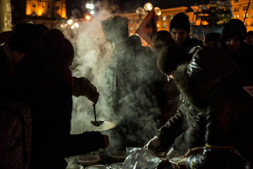 KIEV, UKRAINE - DECEMBER 5: Anti-government protesters lined up for a dinner of hot soup on December 5, 2013 in Kiev, Ukraine. Thousands of people have been protesting against the government since a decision by Ukrainian president Viktor Yanukovych to suspend a trade and partnership agreement with the European Union in favor of incentives from Russia. (Photo by Brendan Hoffman/Getty Images) *** Local Caption ***