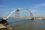 Nederland, Nijmegen, 24-04-2013De Nijmeegse stadsbrug De Oversteek is over de Waal gelegd en rust zijn pijlers.  De Oversteek is een boogbrug van 285 meter lang en 60 meter hoog en is de op een na langste hoofdoverspanning van Nederland, en de grootste boogbrug van Europa met een enkelvoudige boog. Hij dankt zijn naam aan de heldhaftige oversteek over de Waal van amerikaanse parachutisten van de 82nd airborne division tijdens de oparatie Market Garden in de Tweede wereldoorlog die precies op deze plaats plaatsvond. De nieuwe brug moet zorgen voor een betere spreiding en doorstroming van verkeer binnen de stad Nijmegen. Na 75 jaar is er eindelijk een tweede vaste oeververbinding voor de stad. De oude waalbrug krijgt vanaf eind dit jaar groot onderhoud, waarna de volle capaciteit van beide bruggen pas gebruikt kan worden. De skyline van de stad is voorgoed veranderd.Foto: Flip Franssen/Hollandse Hoogte