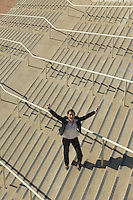Businesswoman standing on stairs and yelling with arms raised, elevated view