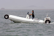 Sealegs amphibious rigid inflatable boat with Evinrude outboard motor. RIB fitted with hydraulicly motorized wheels on hydraulic legs that lower the wheels into place for travel on dry land.