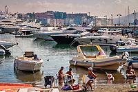 Quartier de Posillipo<br /> Les plages napolitaines sont toutes privees et hors de prix.<br /> Les napolitains sont contraints de se baigner au milieu des bateaux<br /> <br /> Naples fut d'abord fondee au cours du viie&nbsp;siecle avant notre ere sous le nom de Parthenope par la colonie grecque de Cumes. <br /> Ce premier etablissement fut appele Palaiopolis (la ville ancienne). <br /> Lorsqu'une seconde ville fut fondee vers 500 avant notre ere par de nouveaux colons, cette nouvelle fondation fut appelee Neapolis (nouvelle ville).<br /> Alliee de Rome au ive&nbsp;siecle av.&nbsp;J.-C., la ville conserve longtemps sa culture grecque et restera la ville la plus peuplee de la botte italique et sans aucun doute sa veritable capitale culturelle.<br /> Elle rempla&ccedil;a Capoue comme capitale de la Campanie apres la bataille de Zama, a la suite de la confiscation de citoyennete et des territoires de cette derniere, par son alliance avec Hannibal avant la bataille de Cannes.<br /> Naples possede ainsi l'une des plus grandes concentrations au monde de ressources culturelles et de monuments historiques, jalonnant 2800 ans d'histoire. <br /> Dans le centre historique, inscrit sur la liste du patrimoine mondial de l'Unesco, se rencontrent notamment 448 eglises historiques ainsi que d'innombrables palais historiques, fontaines, vestiges antiques, villas, residences royales.