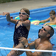 BURNCAMP - OKOBOJI, JULY 15 -- Cedar Falls firefighter John Bostwick lifts camper Caryn Stewart as they play in the Camp Foster pool Thursday.  Bostwick is one of many professionals who volunteers his time during the Miracle Burn Camp week in Okoboji.  Photo by David Peterson