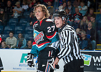 KELOWNA, CANADA, OCTOBER 16 -  Ryan Olsen #27 of the Kelowna Rockets is escorted to the penalty box by linesman Kevin Crowell on Wednesday, October 16, 2013 at Prospera Place in Kelowna, British Columbia (photo by Marissa Baecker/Getty Images)***Local Caption***