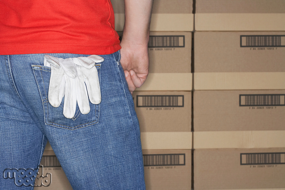 Warehouse Worker standing in front of stacks of boxes gloves hanging out of back pocket mid section back view