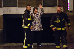 © licensed to London News Pictures. London, UK 27/02/2014. A woman thanking to a fireman after being carried across the street by fire brigade where a burst main has flooded Clapham Road in south London on Thursday, 27 February 2014. Photo credit: Tolga Akmen/LNP