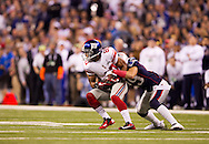 INDIANAPOLIS, IN - FEBRUARY 05:  Victor Cruz #80 of the New York Giants is hit by  Sterling Moore #29 of the New England Patriots during Super Bowl XLVI at Lucas Oil Stadium on February 5, 2012. (Photo by Tom Hauck)