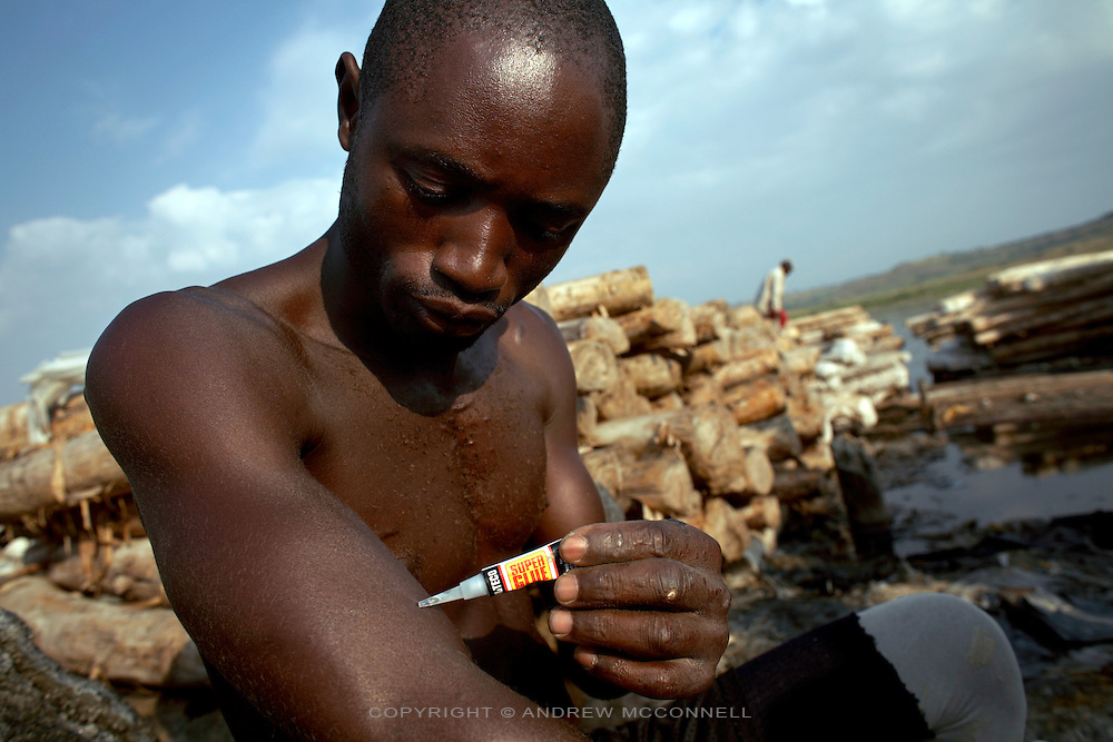 A man applies Super Glue to broken skin on his arm before entering the water to extract rock salt at Lake Katwe, Uganda, on Saturday, Dec. 29, 2007. The extraction of rock salt requires men to enter the main body of the lake and work in water up to their chests. Any cut or nick in the skin gets eaten at by the chemicals in the water making the wound bigger. The only option for the men, who cannot afford to take time off to allow a laceration to heal, is to apply strong glue over the wound in order to keep the salt water and the chemicals it contains out.