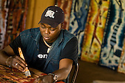 An artisan paints in his shop at the Village Artisanal de Ouagadougou, a cooperative that employs dozens of artisans who work in different mediums, in Ouagadougou, Burkina Faso, on Monday November 3, 2008.