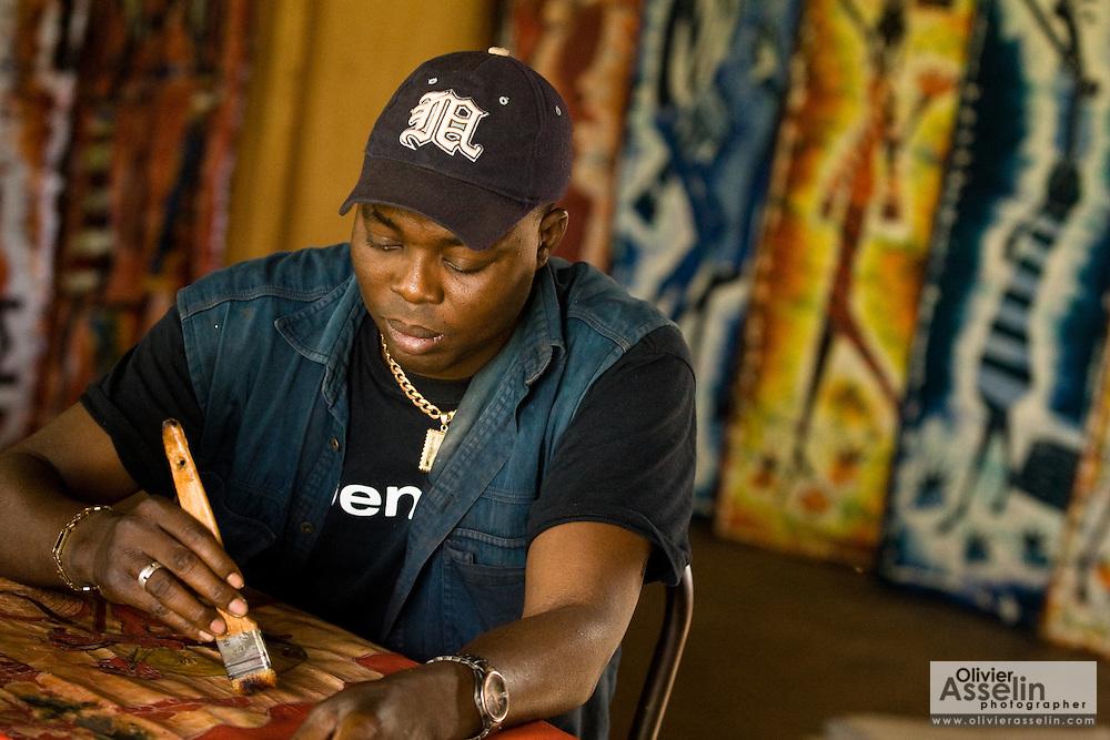 An artisan paints in his shop at the Village Artisanal de Ouagadougou, a cooperative that employs dozens of artisans who work in different mediums, in Ouagadougou, Burkina Faso, on Monday November 3, 2008.