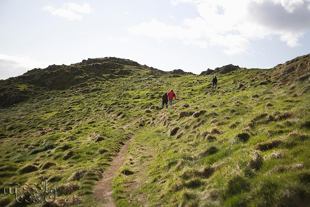 Three adults climbing a hillside