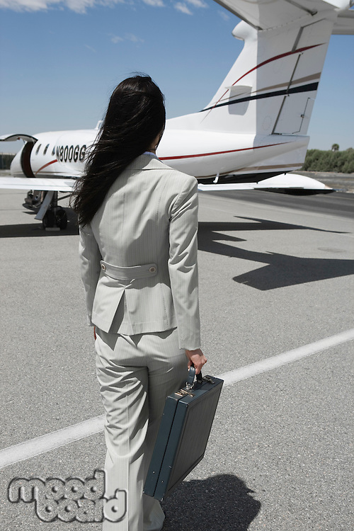 Mid-adult businesswoman walking towards private jet.