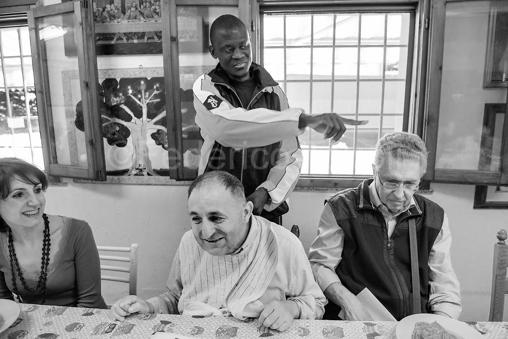 Maniame Bathily belonging from Mali and hosted by Caritas of Modena diocese., at lunch with other guests of the Casa della Carità  where he lives