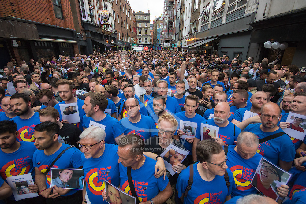 Old Compton Street, Soho, London, June 13th 2016. Thousands of LGBT people and their friends converge on Old Compton Street in London's Soho to remember the fifty lives lost in the attack on gay bar Pulse in Orlando, Florida. PICTURED: The London Gay Men's Chorus each hold a picture of one of the victims ahead of an emotional performance of Bridge over Troubled Water.