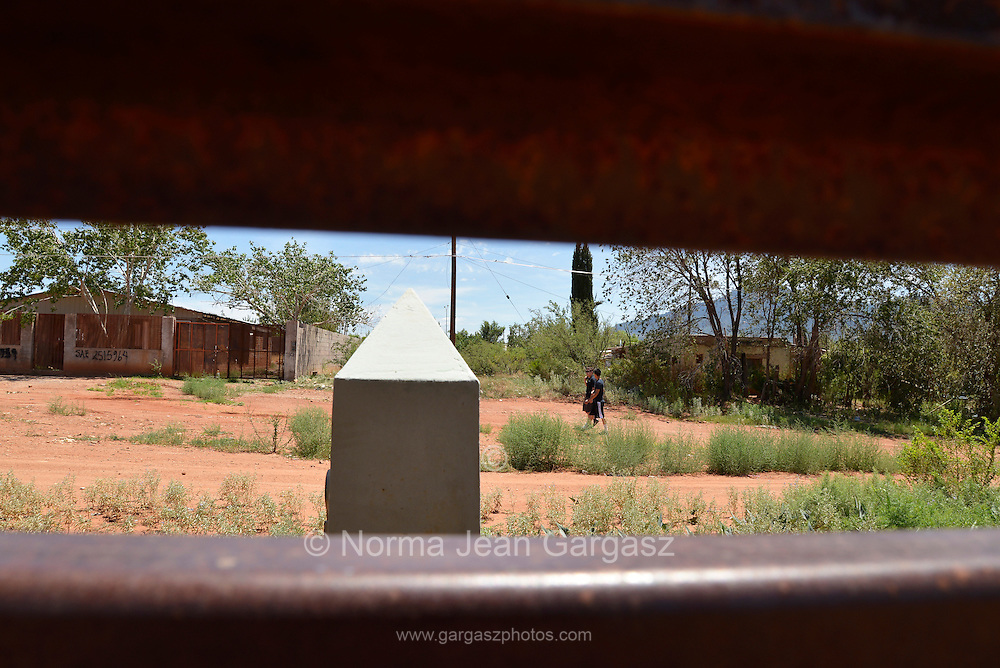Teens walk down a road in Naco, Sonora, Mexico along the international border with Naco, Arizona, USA.  The two are seen through a gap in the metal wall, which was constructed next to the concrete pillar that originally indicated the international line.